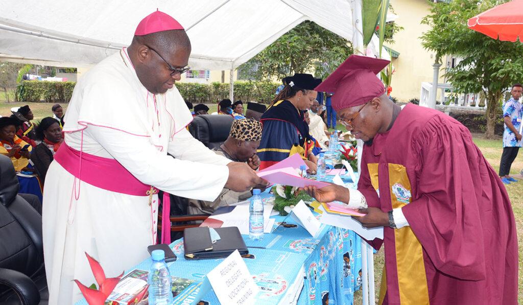 Bishop handing attestation to Graduate